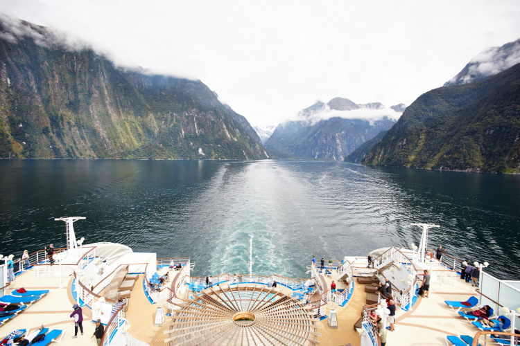 A Princess Cruise ship sailing through a fjord in Fiorland National Park